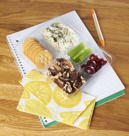 writing utensil: Salad, crackers, nuts, celery and grapes in a plastic box as a snack