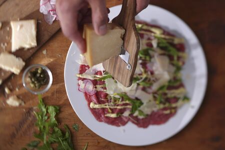 parer: Parmesan being grated over beef carpaccio