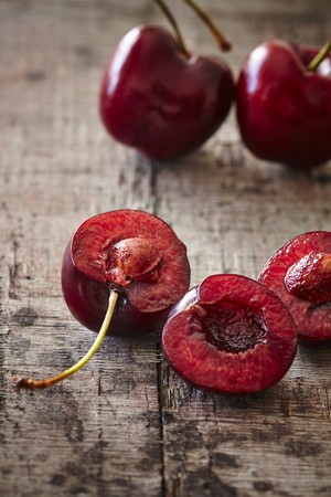 halved  half: Fresh Spanish cherries on a wooden board LANG_EVOIMAGES
