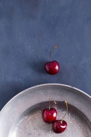 plater: Sweet cherries on a pewter plater sprinkled with sugar