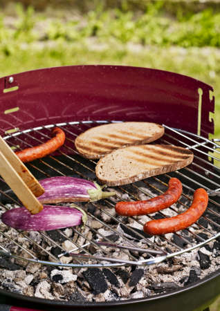 Sausages, aubergines and slices of bread on a barbecue LANG_EVOIMAGES
