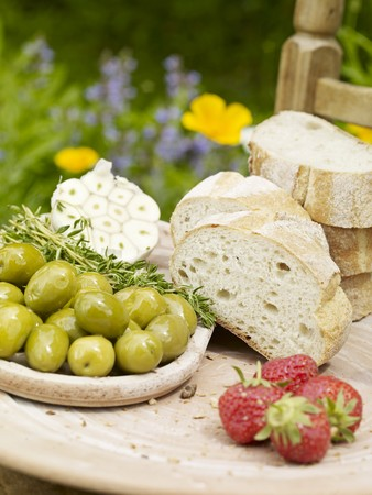 A sliced Milan baguette with olives, strawberries and garlic on a wooden board in the garden