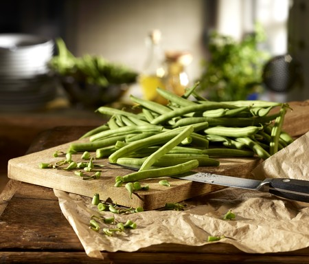 cleaned: Green beans being chopped on a wooden board in a kitchen