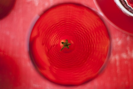 ides: A view from above of a red drinking glass garnished with a cocktail tomato LANG_EVOIMAGES