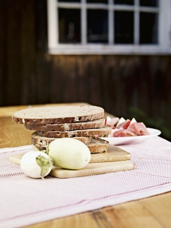 Sliced rye bread, white aubergines and raw ham on a table