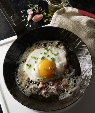 pancetta cubetti: Un uovo fritto con pancetta a dadini e erba cipollina in una calda panna nera