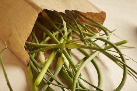 Organic garlic stems in a brown paper bag LANG_EVOIMAGES
