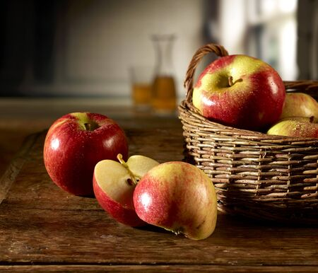 Red apples in a basket on a wooden table, one apple sliced LANG_EVOIMAGES
