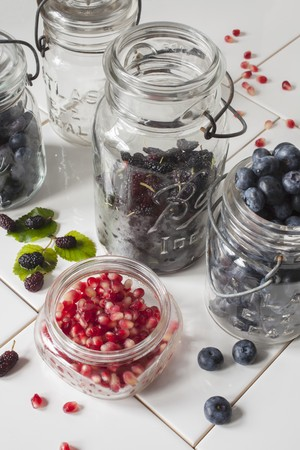 Fresh blueberries, mulberries and pomegranate seeds in preserving jars on white tiles