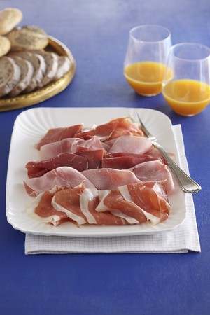 whiteness: A ham platter with bread and fruit juice
