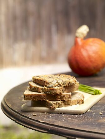 pit fall: Slices of pumpkin seed bread, stacked, on a rustic garden table LANG_EVOIMAGES
