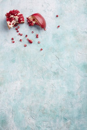 breaking: A broken pomegranate on a blue surface LANG_EVOIMAGES