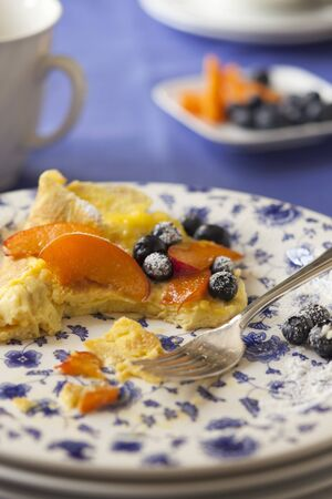 food: Sweet omelette with blueberries, peaches and icing sugar, partially eaten