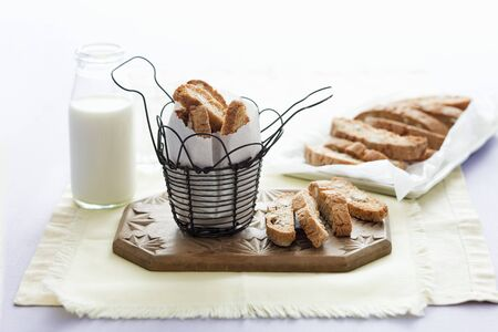 bakery products: Cantucci in a wire basket and on a chopping board