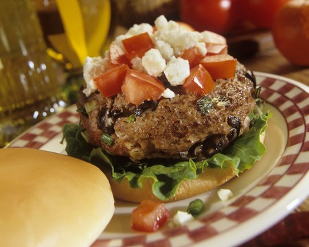 A Greek burger with black olives, chopped tomatoes and feta cheese