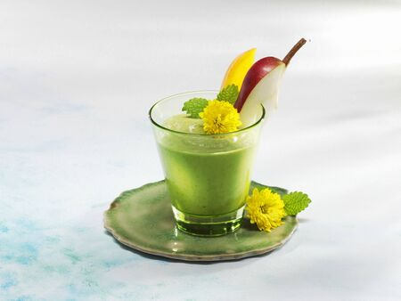 A mango and spinach smoothie garnished with flowers LANG_EVOIMAGES
