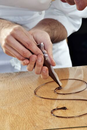 Chocolate sauce being piped onto a glass platter