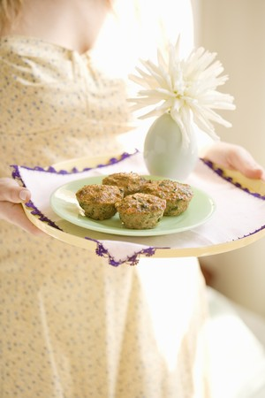 A woman holding a tray of savoury cupcakes made from minced beef and vegetables LANG_EVOIMAGES