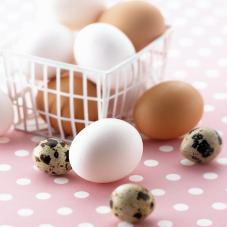 Brown and white eggs in a plastic basket and quails eggs LANG_EVOIMAGES