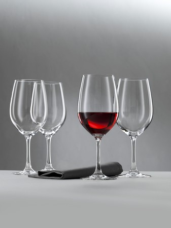 A glass of red wine and three empty wine glasses against a grey background LANG_EVOIMAGES