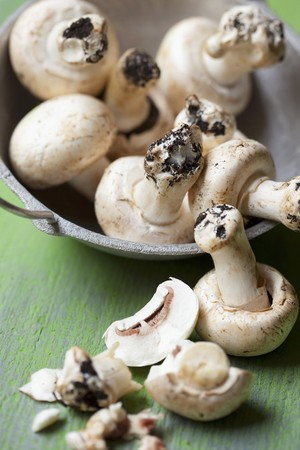 Fresh mushrooms with soil in and in front of a bowl