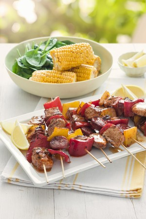 Pork skewers with peppers served with corn cobs