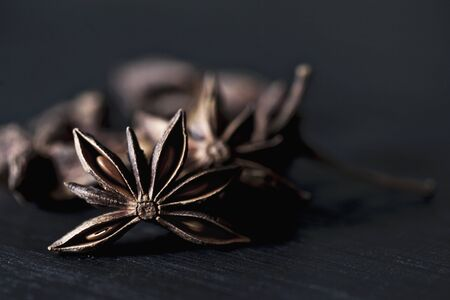 Star anise on a black wooden table LANG_EVOIMAGES