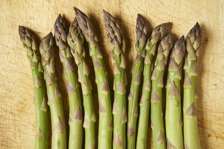 A row of green asparagus spears on a wooden board