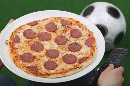 provenance: Hands holding salami pizza and remote, football