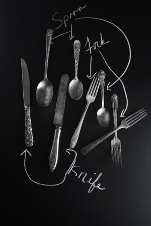 writing utensil: Old knives, spoons and forks on a slate surface with labels