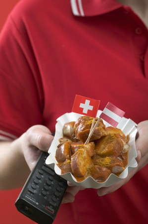 provenance: Footballer holding currywurst (sausage with curry sauce) & remote LANG_EVOIMAGES
