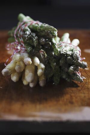 Bundles of white and green asparagus on a chopping board LANG_EVOIMAGES