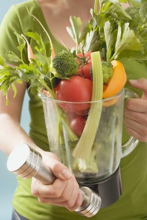 Woman holding hand weight & fresh vegetables in liquidiser