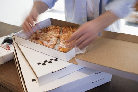provenance: Man dividing up Pizza Margherita in pizza box LANG_EVOIMAGES