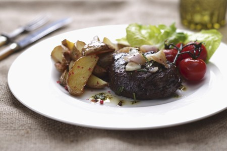 Rump steak with potato wedges and cherry tomatoes LANG_EVOIMAGES