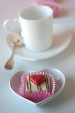 cup four: A petit four decorated with a heart in front of a mocha cup LANG_EVOIMAGES