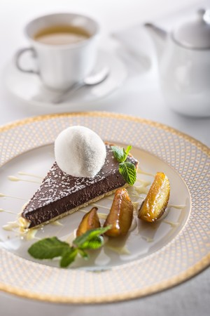 gateau: Chocolate tart with creme anglaise, pears and a scoop of milk ice cream on a festive plate