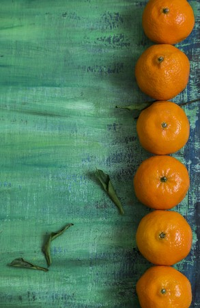 clementines: A row of clementines on a turquoise surface LANG_EVOIMAGES