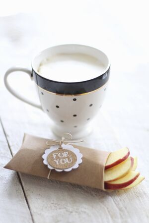 A cup of cafe au lait and fresh apple slices