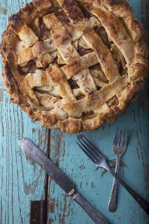 An apple pie and old cutlery (seen from above)