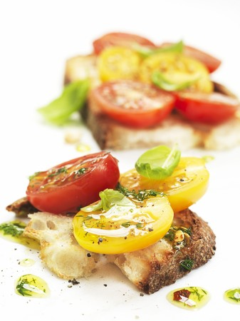 Bruschetta topped with red and yellow tomatoes LANG_EVOIMAGES