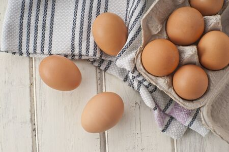 Brown eggs in an egg box and next to it LANG_EVOIMAGES