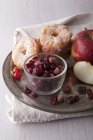 Apple doughnuts with sugar, candied fruit and fresh apples