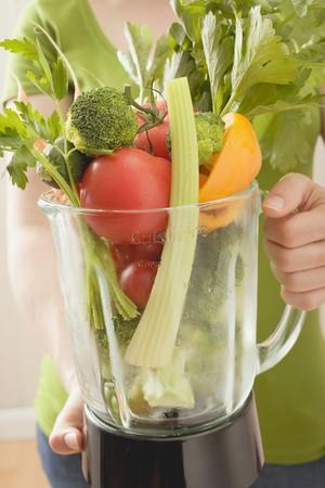 Woman holding fresh vegetables in liquidiser