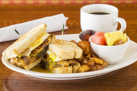 A breakfast sandwich with fried potatoes, fruit salad and coffee