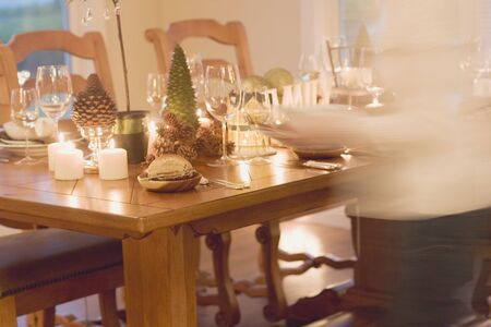 provenance: Woman bringing plates to table laid for Christmas