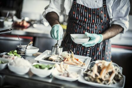 A chef arranging a plate of appetisers