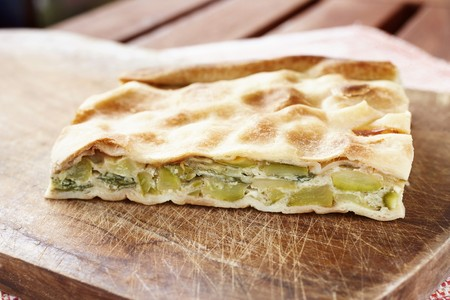 A slice of courgette, egg and quark pie with flaky pastry on a wooden chopping board
