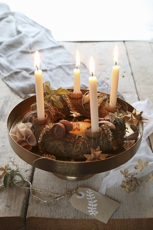 guirnaldas de navidad: A traditional advent wreath on a golden stand with a hand painted label on a rustic table LANG_EVOIMAGES