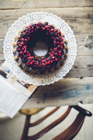 coatings: A ring-shaped Bundt cake with berries and chocolate glazing